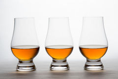 Whiskey in tre Crystal Tasting Glasses Fotografia Stock