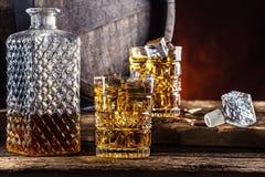 whiskey Två koppar som är fulla av dryckwhiskykonjak eller konjak med iskuber i retro stil Gammal ektrumma i bakgrunden royaltyfri fotografi