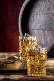 whiskey Två koppar som är fulla av dryckwhiskykonjak eller konjak med iskuber i retro stil Gammal ektrumma i bakgrunden arkivfoto