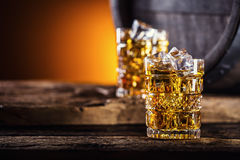 Whiskey. Two cups full of beverage whiskey brandy or cognac with ice cubes in retro style. Old oak barrel in the background Royalty Free Stock Image