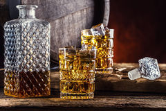 Whiskey. Two cups full of beverage whiskey brandy or cognac with ice cubes in retro style. Old oak barrel in the background Royalty Free Stock Photography