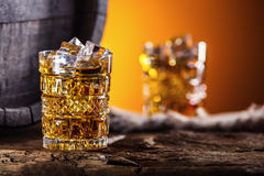 Whiskey. Two cups full of beverage whiskey brandy or cognac with ice cubes in retro style. Old oak barrel in the background Royalty Free Stock Photos