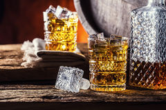 Whiskey. Two cups full of beverage whiskey brandy or cognac with ice cubes in retro style. Old oak barrel in the background Stock Photography