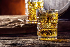 Whiskey. Two cups full of beverage whiskey brandy or cognac with ice cubes in retro style. Old oak barrel in the background Stock Images