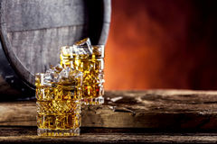 Whiskey. Two cups full of beverage whiskey brandy or cognac with ice cubes in retro style. Old oak barrel in the background Stock Photos