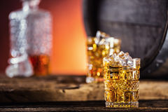 Whiskey. Two cups full of beverage whiskey brandy or cognac with ice cubes in retro style. Old oak barrel in the background Royalty Free Stock Photo