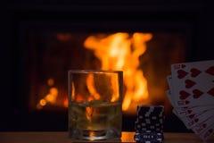 Whiskey in vetri dal camino alla notte Immagini Stock Libere da Diritti