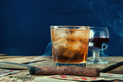 Whiskey,wine, cigar and cards on a wooden background Royalty Free Stock Image