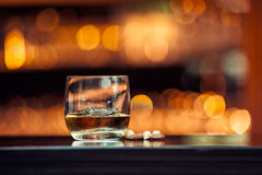 Whiskey on wood bar. Glass of whiskey on a wooden table bar on the background of bright lights of the bar stock images