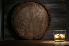 Whiskey on a wooden. Background in the darkness, drawn by light and the barrel Stock Images
