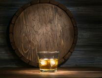 Whiskey on a wooden. Background in the darkness, drawn by light and the barrel Stock Photography