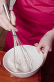 Whisking in bowl. A woman whisking  something in a bowl Royalty Free Stock Images