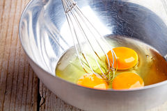 Whisking eggs in metal bowl Stock Images