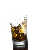 Whisky écossais éclaboussant hors du verre d'isolement en fonction Photographie stock