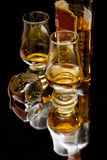Whisky. Two glasses of whisky with watch and bottle reflected and isolated on black Royalty Free Stock Images