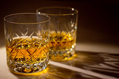 Whisky. Two cut crystal whisky glasses with whisky Royalty Free Stock Images