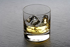 Whisky. A tumbler with wisky on the rocks Royalty Free Stock Photos