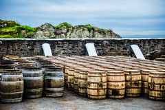 Whisky Barrels by the Sea. Whisky barrels line a wall at a seaside distillery on the isle of Islay, Scotland Stock Photos