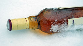 Whisky Bottle in the snow Royalty Free Stock Photography