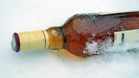 Whisky buteljerar i snowen Royaltyfri Fotografi