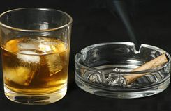 Whisky and cigar. Tumbler of scotch whisky with ice and a smoking cigar Stock Photography
