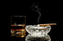 Whisky and a cigar on glossy table Stock Photos