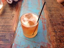 Whisky cocktail in short glass on distressed wooden table. An orange-coloured cocktail (whisky) is served with ice and a straw on a distressed wooden table Royalty Free Stock Photos