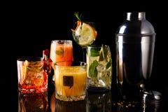 Whisky-cola coctail, mojito-coctail, orange coctail, jordgubbecoctail i glass exponeringsglas med sugrör royaltyfria bilder