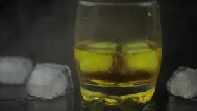 Whisky con ghiaccio Aggiunta dei cubetti di ghiaccio su fondo nero Vetro dell'alcool del rum video d archivio