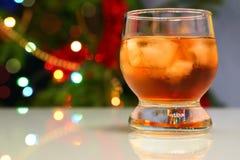 Whisky con hielo contra fondo festivo de las luces fotos de archivo libres de regalías