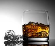 Whisky con hielo en un vidrio transparente en una superficie de cristal Imagen de archivo libre de regalías