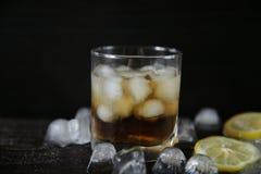 Whisky con hielo en un vidrio en un viejo fondo de madera negro del roble con hielo y el lim?n imagen de archivo