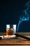 Whisky con hielo y el cigarro en la tabla de madera Imagen de archivo