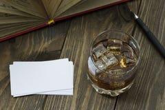 Whisky con hielo y el libro abierto Fotos de archivo libres de regalías