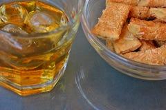 Whisky con hielo y palillos con el queso para un bocado fotos de archivo
