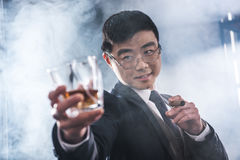 Whisky de consumición del hombre de negocios asiático confiado y cigarro que fuma foto de archivo