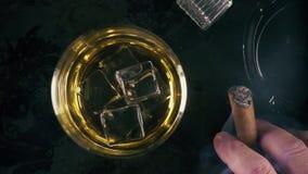 Whisky de la cámara lenta en un vidrio y un cigarro almacen de video
