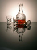 Whisky decanter. And glasses on muted reflection with glowing background Stock Images