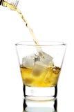 Whisky, der in ein Glas gegossen wird Stockbild