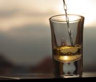 Whisky, der in Schnapsglas gießt Lizenzfreie Stockfotos