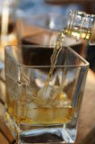 Whisky di versamento nel vetro Fotografie Stock