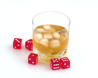 Whisky  and dice. Glass of whisky with ice and red playing bones Royalty Free Stock Photos