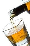 Whisky doble que es vertido en un vidrio Fotos de archivo libres de regalías
