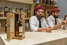 Whisky Dram Festival in Kiev, Ukraine. Unrecognized presenters works on Glenlivet Single Malt Scotch Whisky Highland distillery booth at 3rd Ukrainian Whisky royalty free stock image