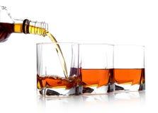 Whisky in drie glazen wordt gegoten dat Stock Afbeeldingen