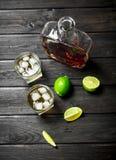 Whisky in een fles en glazen van ijs en plakken van kalk stock foto