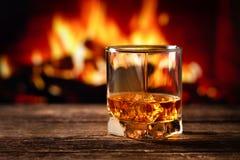 Whisky in een glas met brand in de open haard op de achtergrond stock afbeelding
