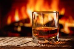 Whisky in een glas met brand in de open haard op de achtergrond stock afbeeldingen