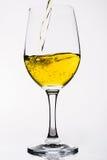 Whisky en una copa de vino aislada en el blanco - amarillo Imagen de archivo libre de regalías