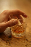 Whisky glass. Crystal glass with whisky with mans hand Stock Images
